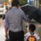 Vater hält Regenschirm über Sohn